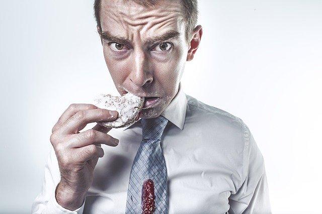 איש לבוש עם עניבה וחולצה אוכל עוגייה