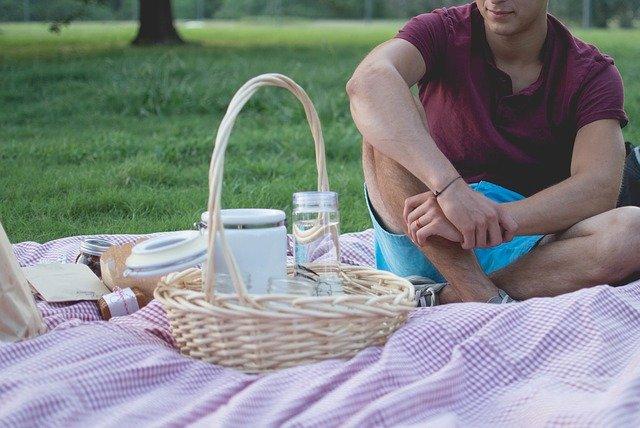 אדם יושב על סדין ודשא עם סלסלה וקופסאות